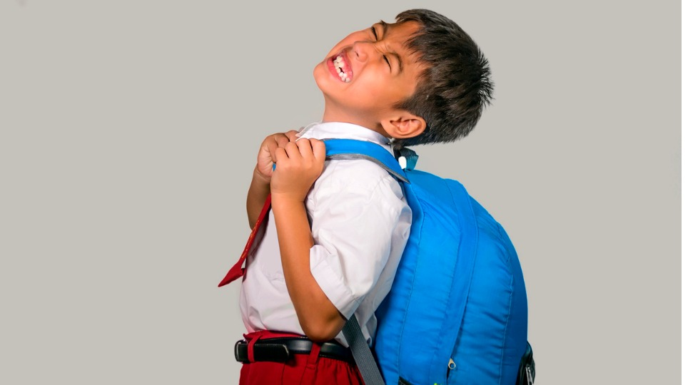 Boy grimacing because of heavy packpack